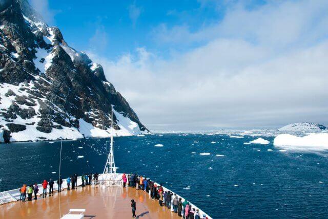 Bergen en een cruiseschip in Antarctica op een zonnige dag.