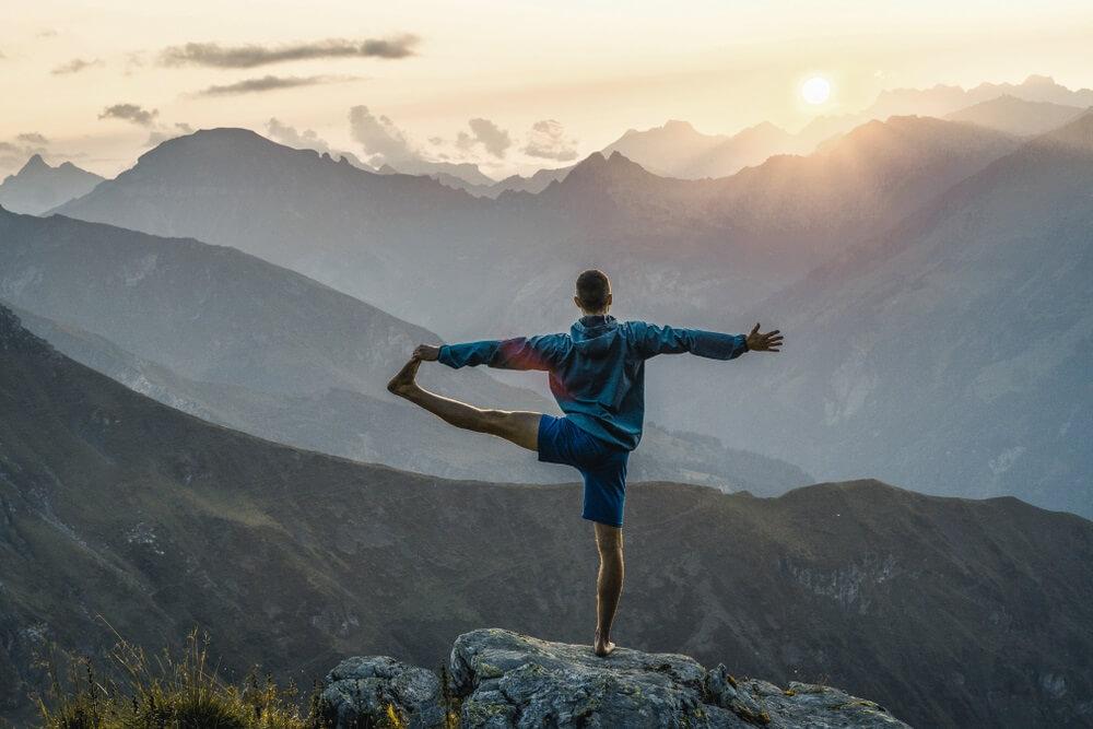 Man die yoga oefeningen doet op de top van een berg in Pizol