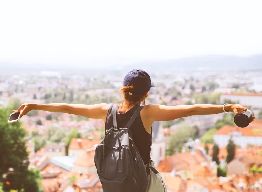 Vrouw die bij een uitzichtpunt in Europa staat, met haar armen wijd