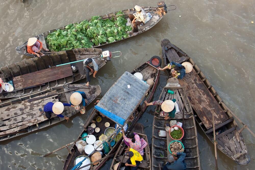 Vietnamezen verkopen hun eten vanuit vissersbootjes op de Mekong Delta