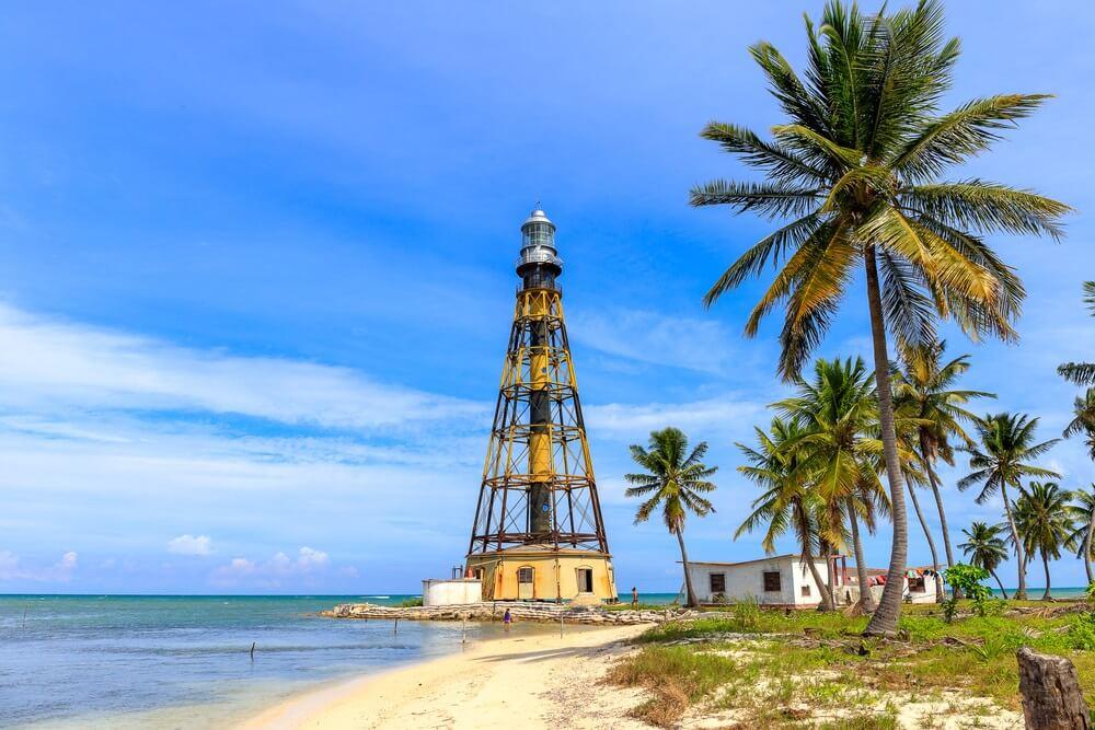 De vuurtoren van Cayo Jutias in Cuba, met palmbomen eromheen en aan weerszijde het strand en de zee.