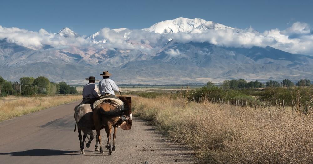 Gaucho's die aan het paardrijden zijn in het Andesgebergte