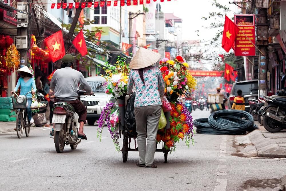 Drukke straat in Hanoi met een bloemverkoper die loopt met de fiets, scooters en een auto, vlaggetjes van Vietnam.