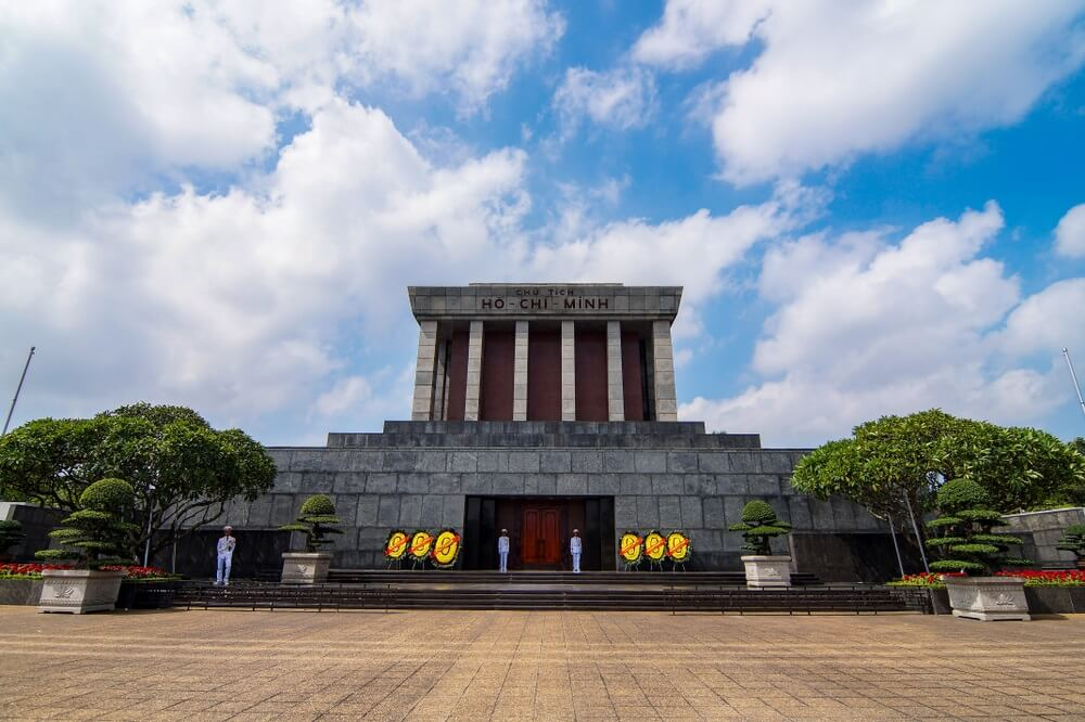 Het mausoleum gebouw van Ho Chi Minh in Hanoi, felblauwe lucht met witte wolken op de achtergrond.