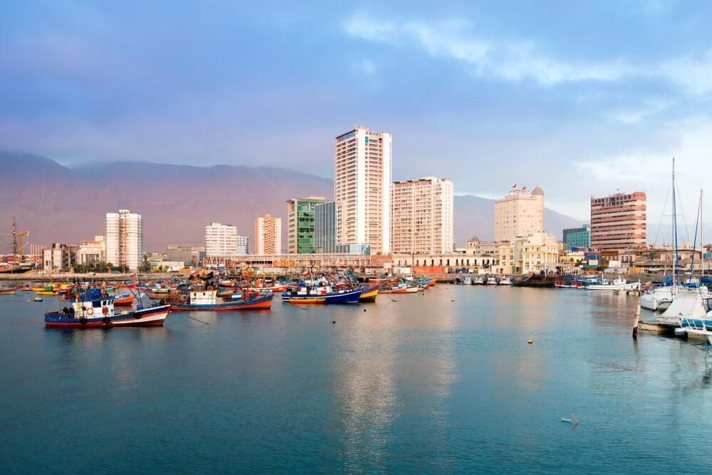 Skyline van de Chileense stad Iquique, met op de voorgrond dobberende bootjes op de oceaan