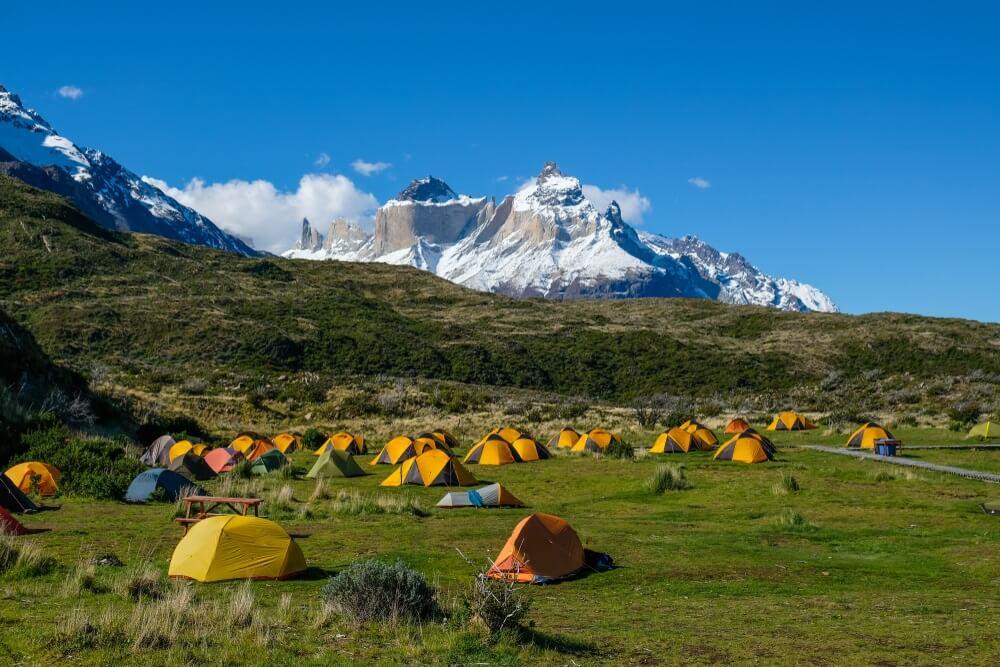 Tientallen gele tentjes die zijn opgezet op een groen grasveld in de natuur van Torres del Paine