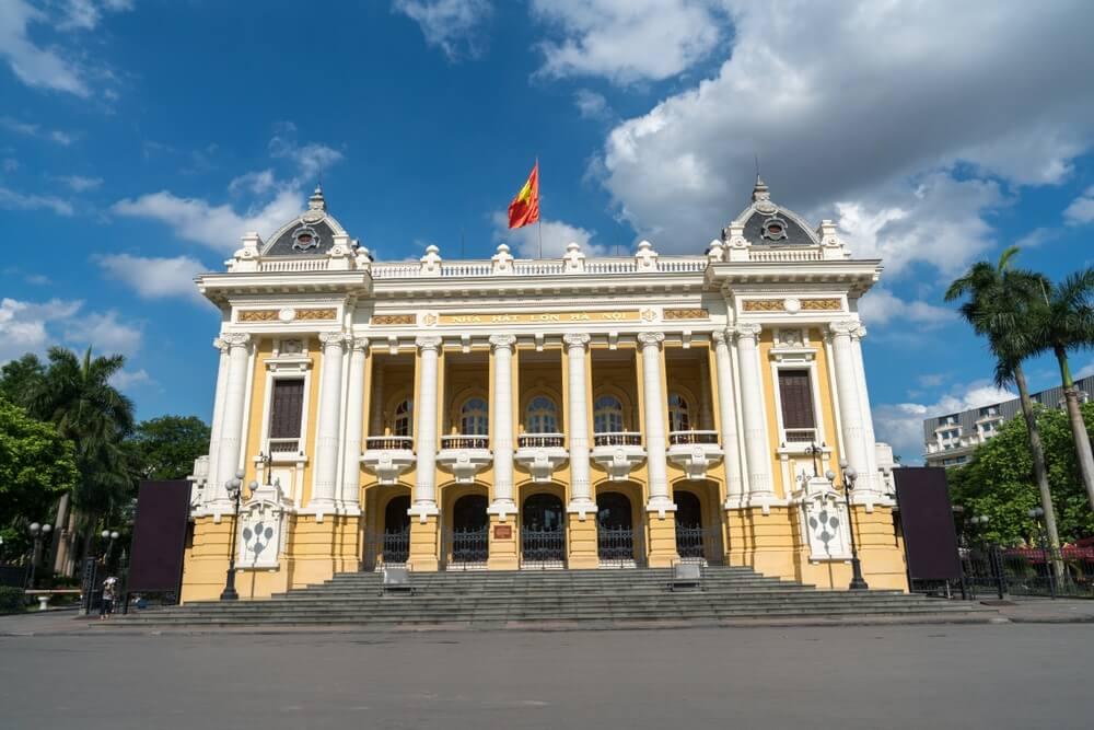 Operagebouw in Hanoi, met zijn Franse architectuur. OP de achtergrond een fel blauwe lucht met witte wolken.