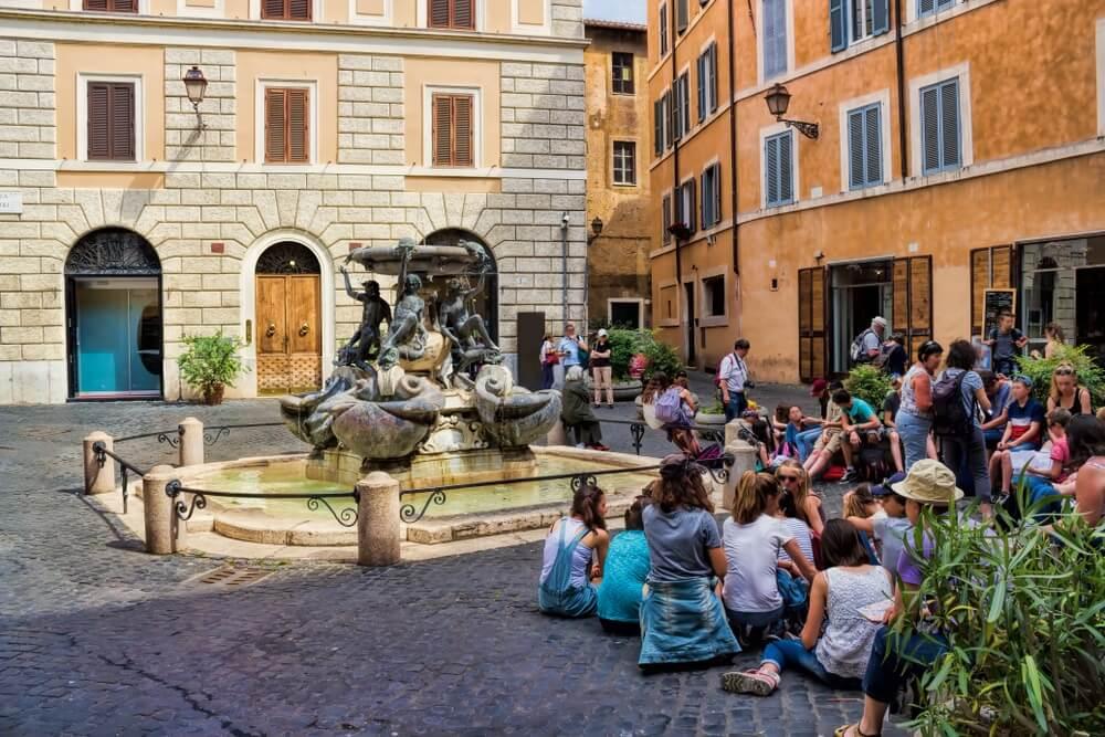 Het kleine Piazza Mattei in Rome met locals die voor de fontein aan het relaxen zijn