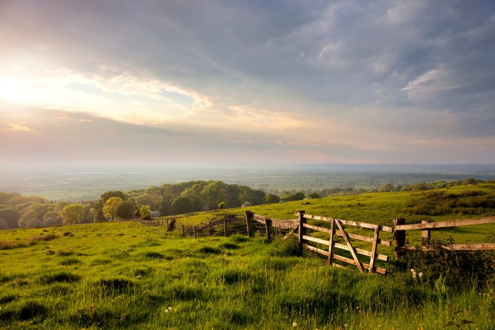 Groene heuvels in het platteland van Engeland met daarboven een blauwe lucht