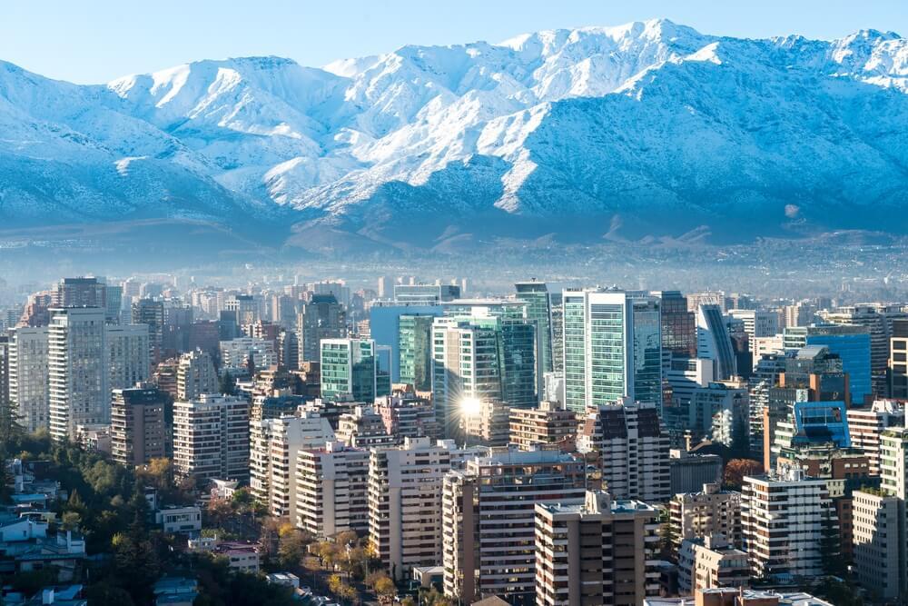 Skyline van Santago de Chile, met op de achtergrond de besneeuwde bergtoppen van de Andes.