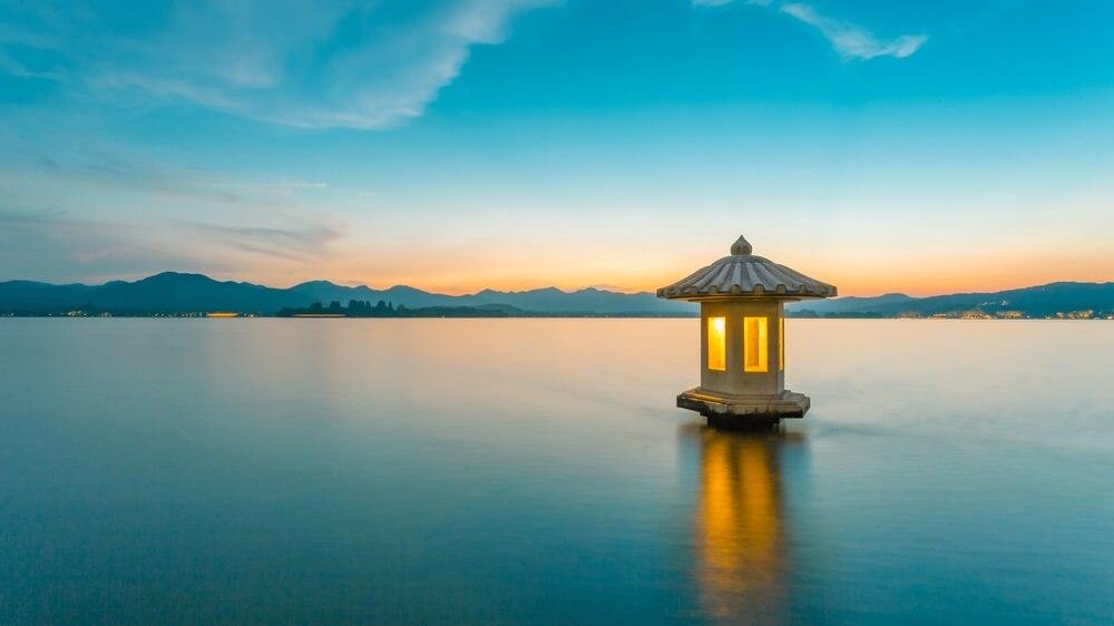 Zonsondergang bij West Lake in Hanoi met een mini tempel op het water en heuvels op de achtergrond.