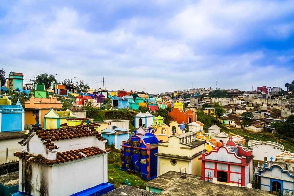 De kleurrijke begraafplaats bij Chichicastenango. Gekleurde graven liggen naast elkaar op een heuvel, blauwe lucht daarboven met enkele wolken.