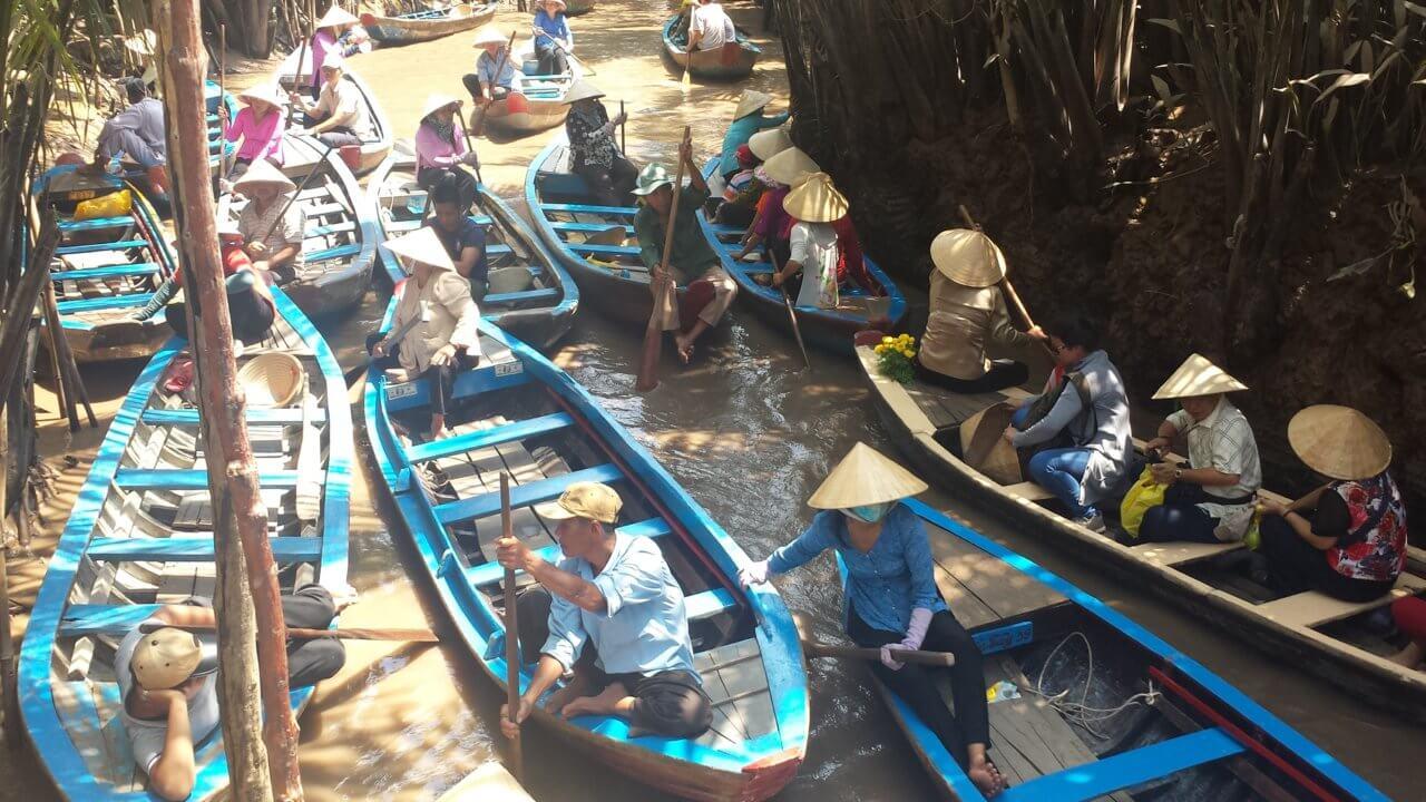 Stuk of 10 houten, blauwe bootjes in de rivier van de Mekong in Vietnam, in de meeste boten zitten 2 tot 4 personen met de typische Vietnamese strohoeden op.