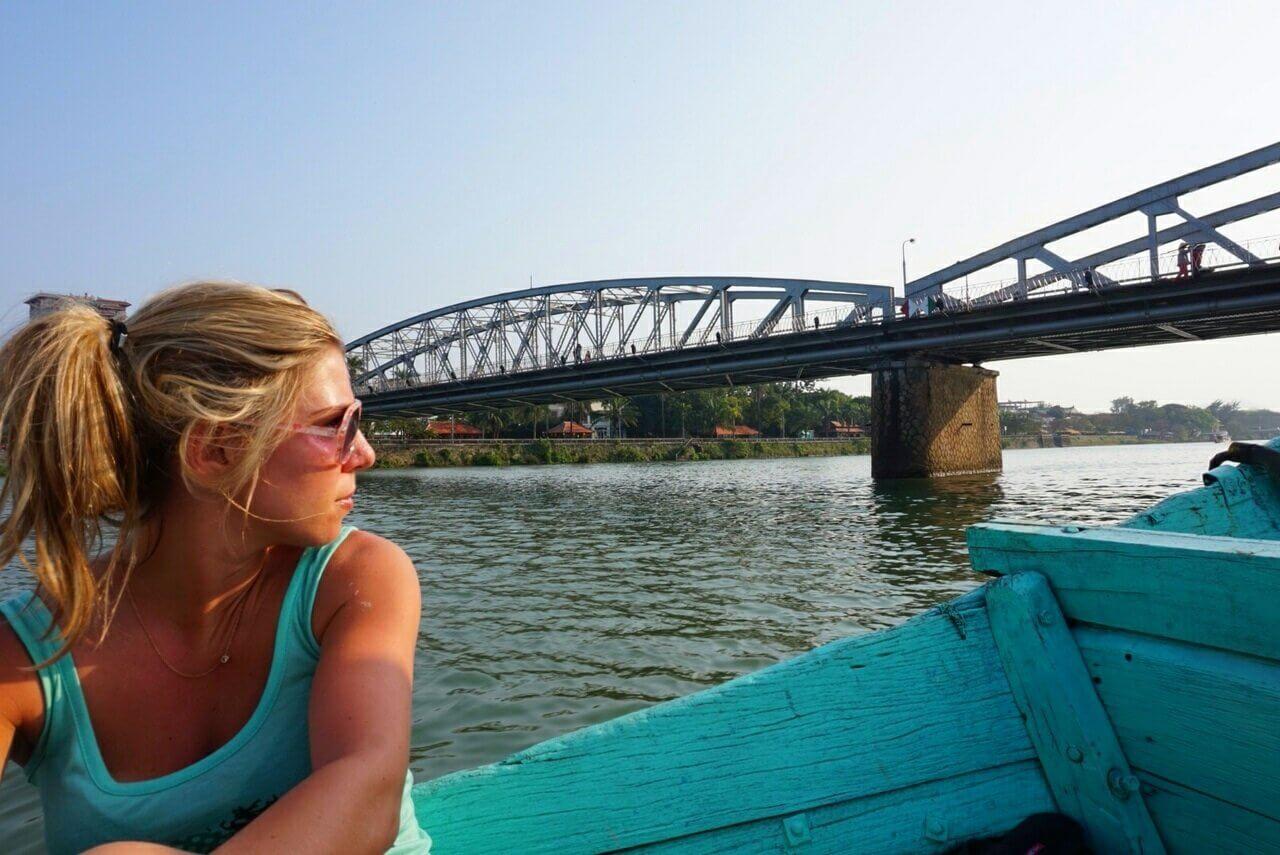 Meisje zit in een blauwe houten boot op de Perfume River in Hue, Vietnam. IJzeren brug op de achtergrond en fel blauwe lucht.