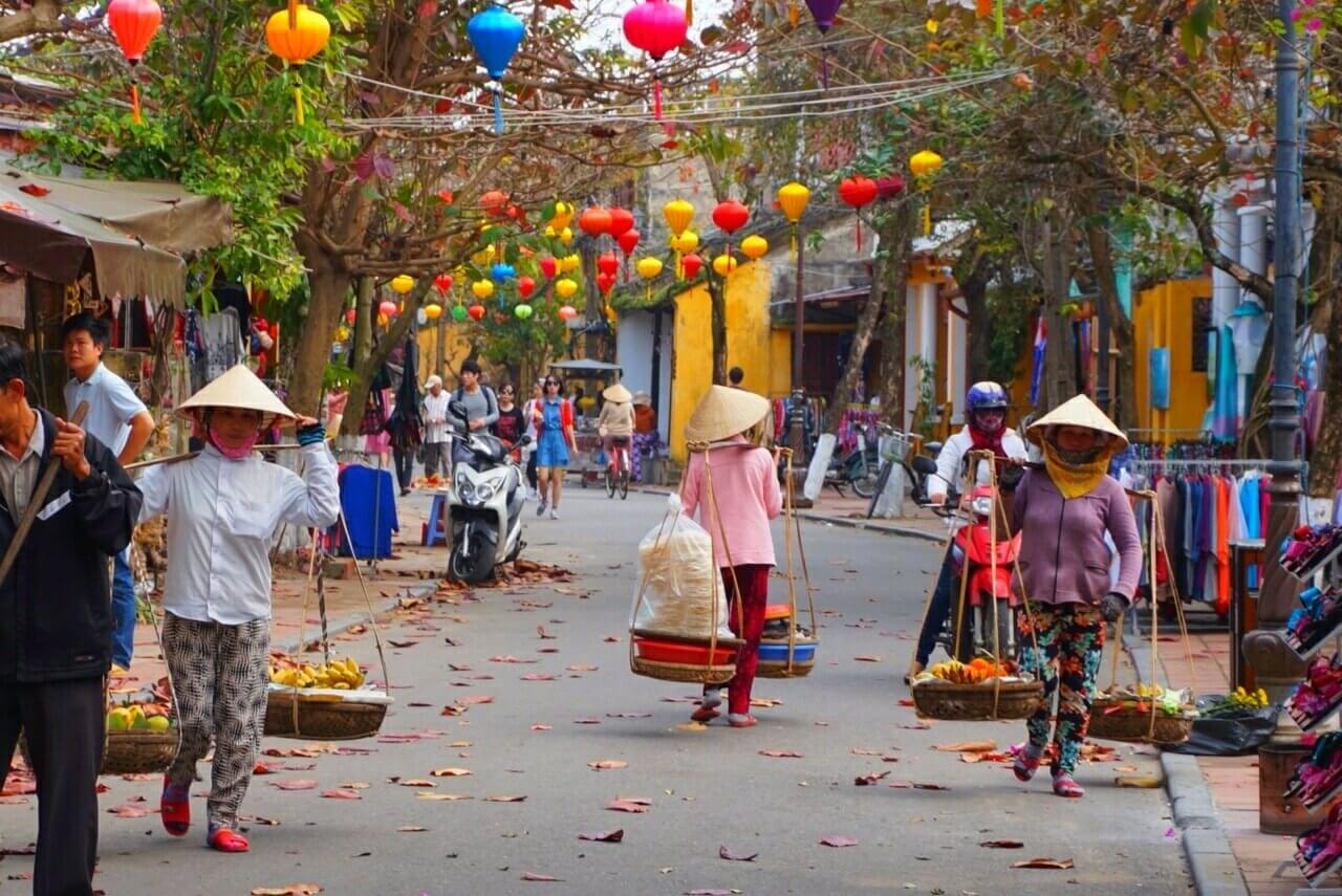 Straatje in Hoi An met Locals die lopen met schalen vol etenswaren en stro hoeden op, gekleurde blaadjes liggen op de grond en er hangen gekleurde lampionnen in de bomen.