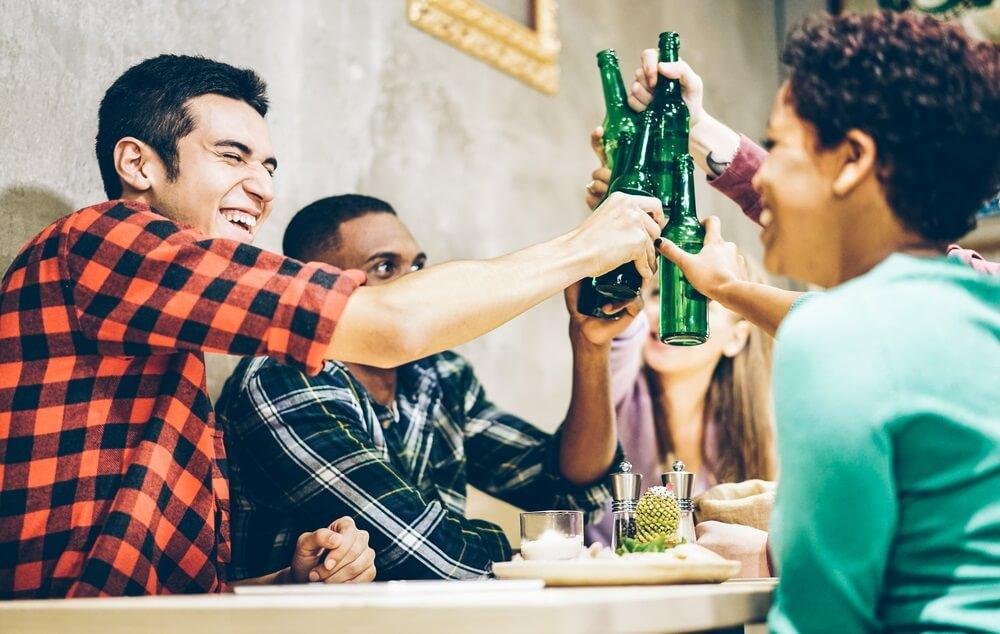 Mensen proosten met flesjes bier in een van de vele kroegen in Dublin.