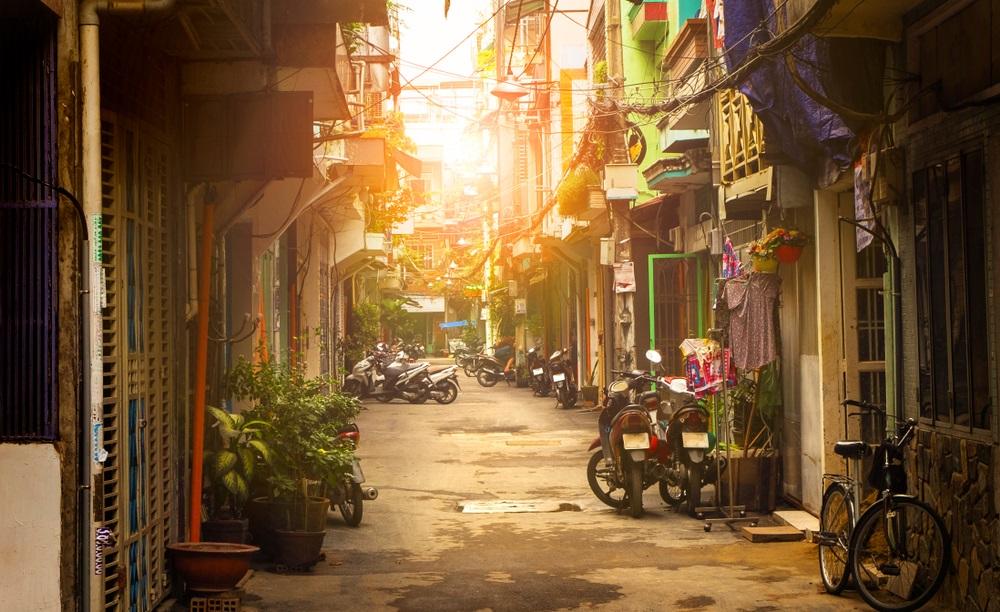 Een van de smalle steegjes van Ho Chi Minh in Vietnam met geparkeerde scooters tegen de gevels van de huizen aan en de gloed van de ondergaande zon op de achtergrond.