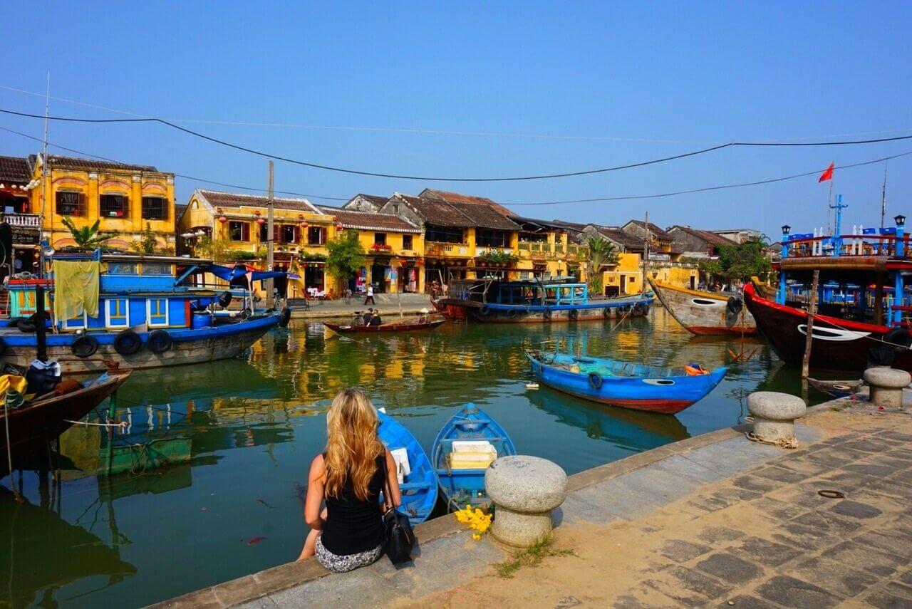 Meisje zit aan de haven van Hoi An en kijkt naar de blauwe bootjes die in het water liggen en de gele huisjes van de overkant die weerspiegelen in het water.