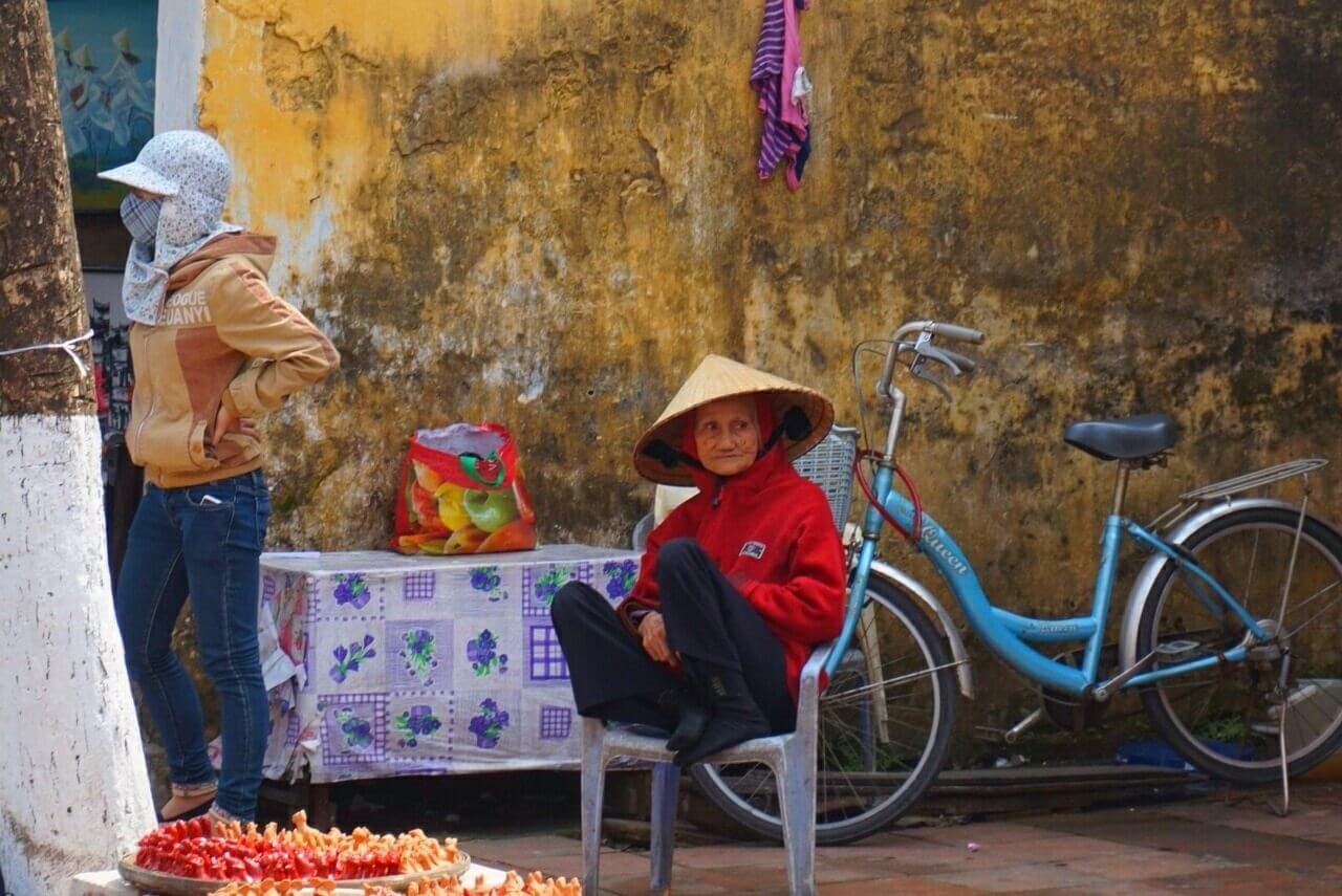 Een oud vrouwtje zit op een plastic stoeltje naast de straatkant met een punthoed op en staart voor zich uit. Haar fiets staat op de achtergrond, en  links staat en man met een pet op een mondkapje op.