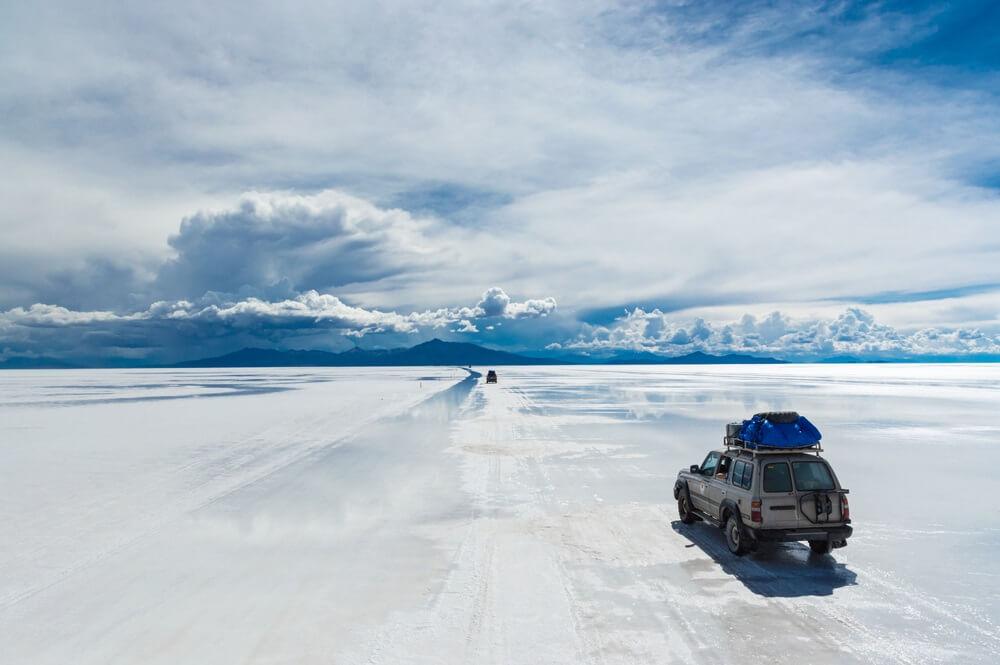 Grijze jeep rijd over de zoutvlakte Salar de Uyuni met bagage op het dak. Aan de horizon witte en grijze wolken.
