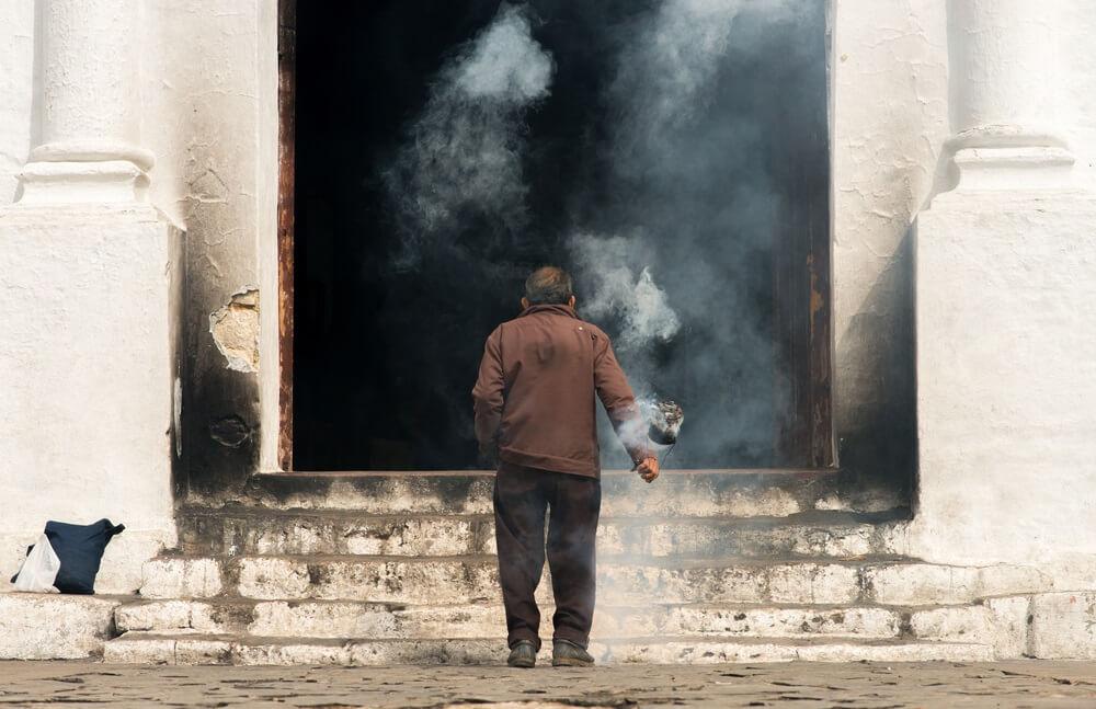 Man die met zijn rug naar het beeld staat, steekt wierook af bij de ingang van de kerk Santo Tomas in Chichicastenango.