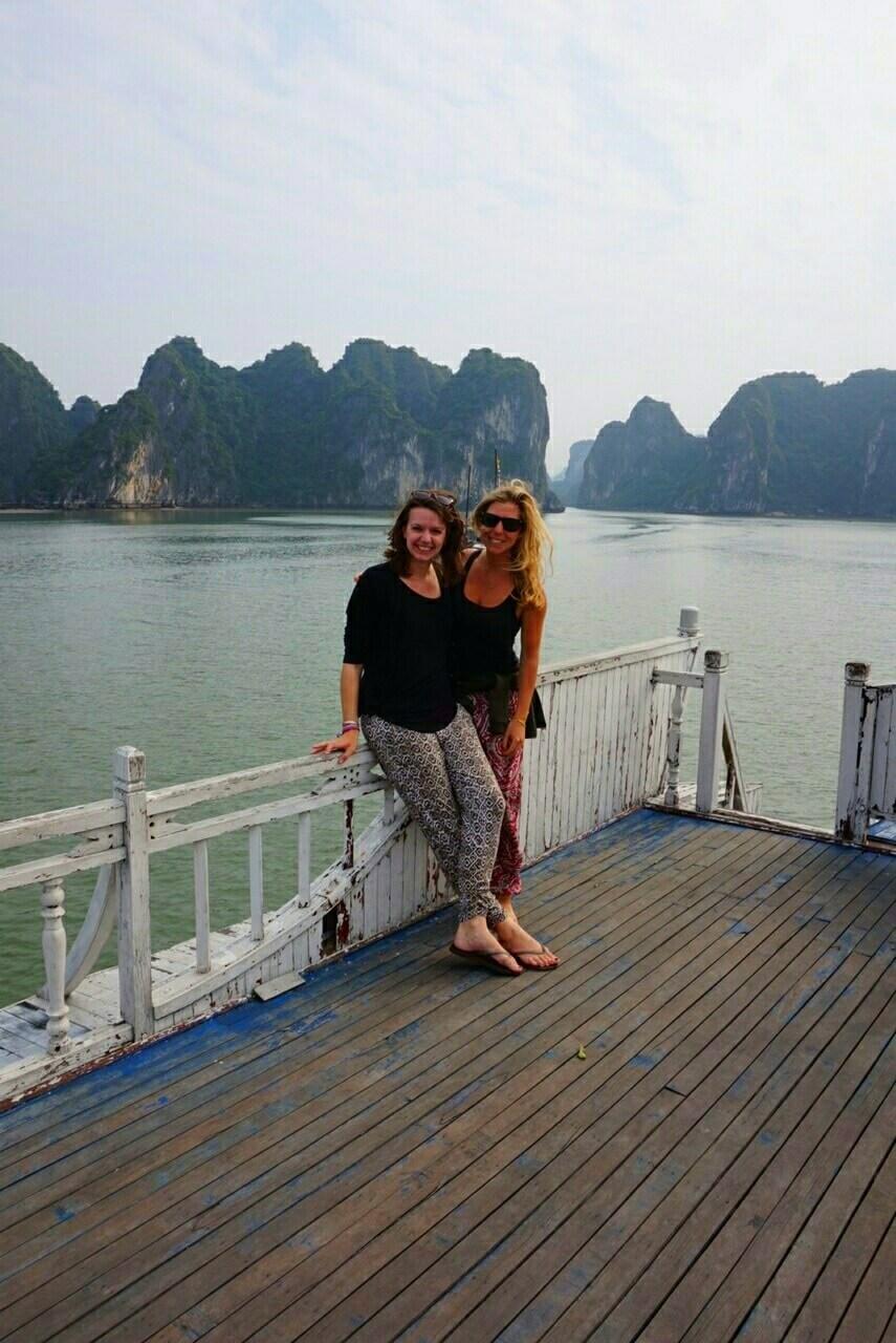 Twee vrouwen op het dek van een tourboot in Halong Bay, Vietnam, zittend op een wit hek. Op de achtergrond steken rotsen uit het water.