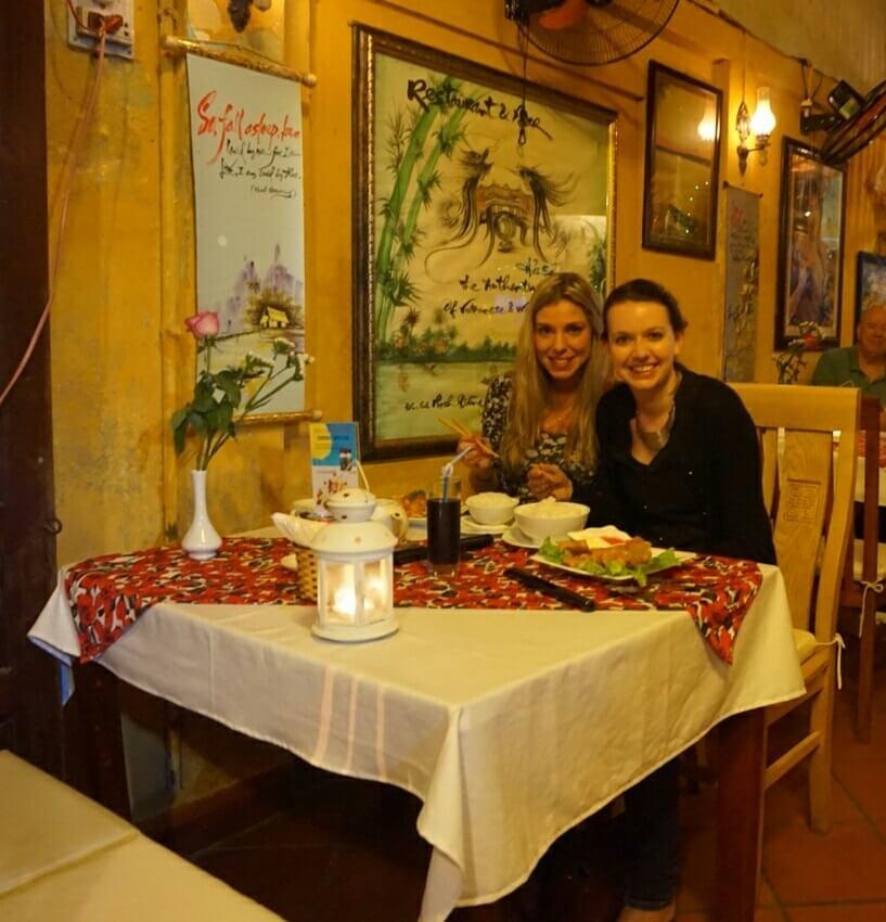 Restaurantje in Hoi An, Vietnam waar twee vrouwen aan een klein tafeltje zitten met Vietnamese gerechten voor zich. Ze lachen in de camera.