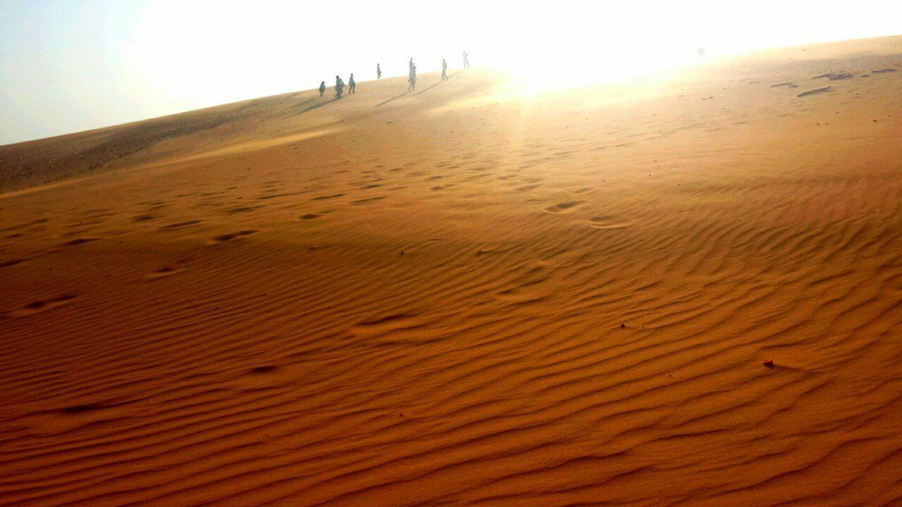 De rode zandduinen van Mui Ne, met de ondergaande zon op de achtergrond en een aantal mensen die op de heuvel van de duin lopen.