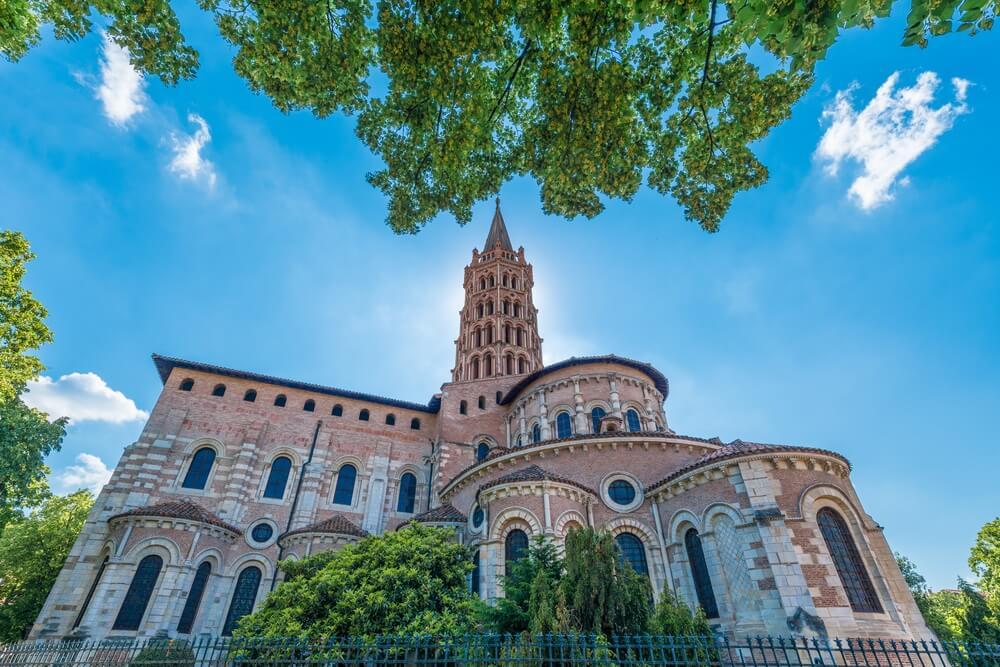 De heilige kerk Saint Sernin, Toulouse. Groene bomen op de voor en achtergrond. Erboven een strakblauwe lucht met een paar kleine witte wolkjes.
