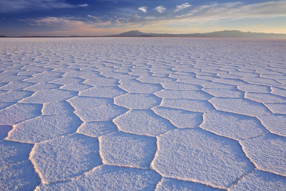 Enorme zoutvlakte Salar de Uyuni, blauwe lucht op de achtergrond en wazige bergen.