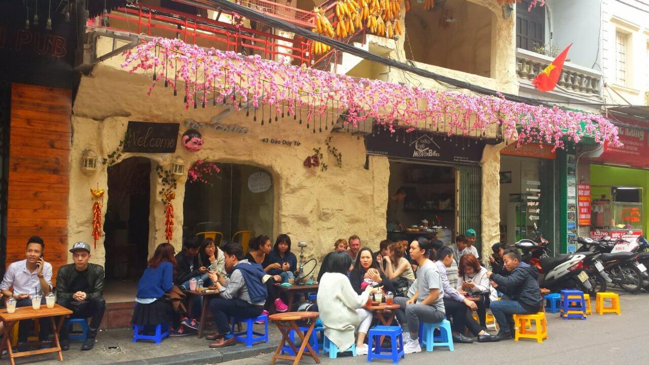 Gezellig terrasje in een straat in Hanoi met mini plastic blauwe en gele stoeltjes en kleine houten tafeltjes. Het hele terras zit vol met mensen, er hangen roze bloemen aan de gevel van het terrasje.