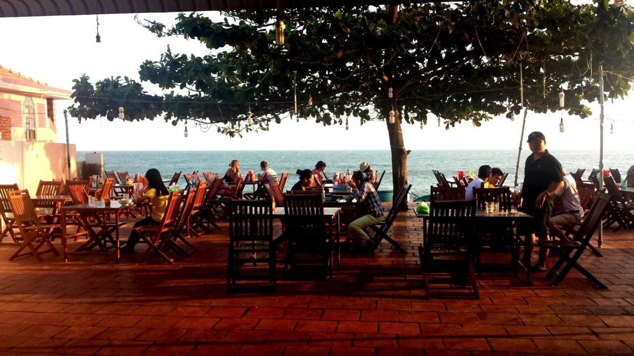 Sfeervol terrasje aan in Mui Ne, met een groene boom in het midden tussen de tafeltjes en de zee op de achtergrond.
