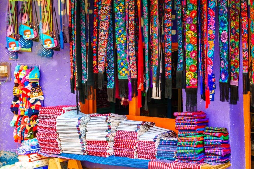 Handgemaakte doeken, tasjes, mutsen en sjaals op de Chichicastenango markt in Guatemala. Allemaal in vrolijke, felle kleurtjes.