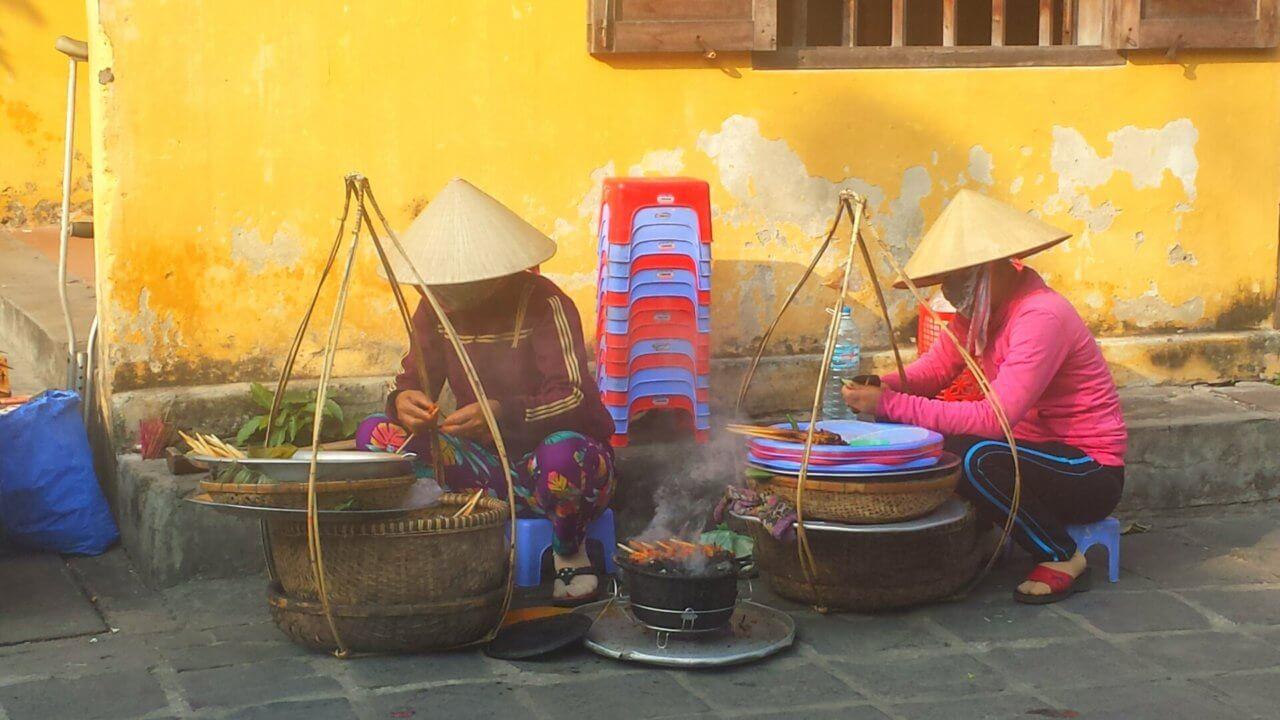 Twee Vietnamezen zitten gehurkt op de grond tegen een gele muur aan en bereiden eten op een klein pannetje. Beide hebben een grote rieten mand naast zich.