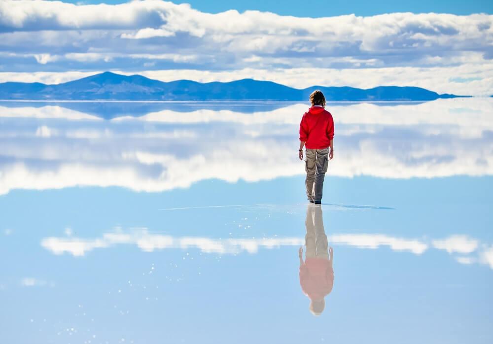 Man met rood jack staat op de zoutvlakte Salar de Uyuni in Bolivia, rug naar de camera toegekeerd, kijkend naar de glooiende bergen aan de horizon.