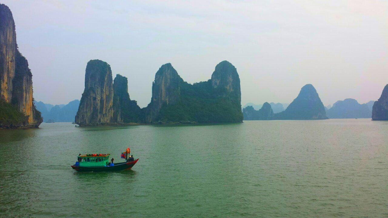 Halong Bay in Vietnam, met rotsen die oprijzen uitde zee en een blauw groen vissersbootje links op de voorgrond. Grijze lucht op de achtergrond.