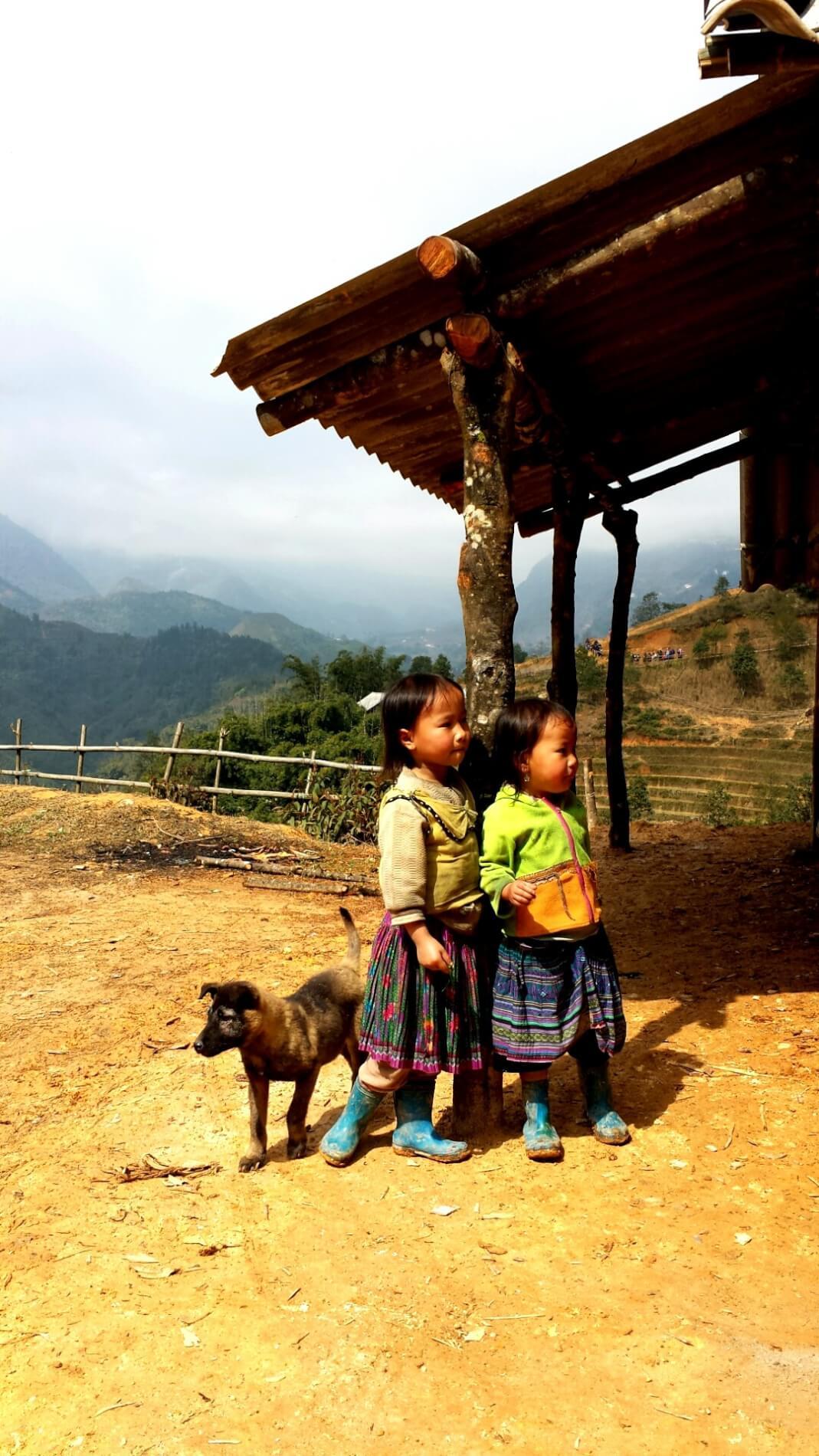 Twee kleine kinderen in traditionele kleding staan naast een houten hutje in Sapa, Vietnam. Links staat een pup naast één van de kindjes. Groene heuvels op de achtergrond.