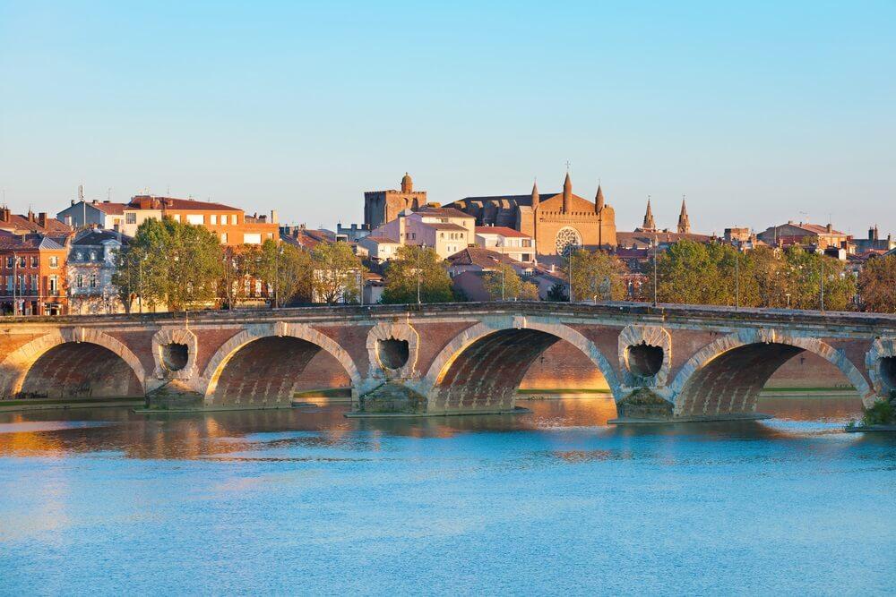 De bekende pont neuf in Toulouse, met de rivier Garonne op de voorgrond. Achter de brug rijzen de gebouwen van de stad op. Op de brug staan enkele groene bomen.