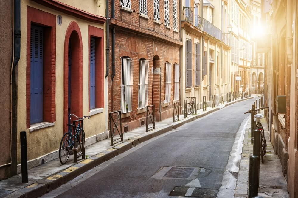 Smal steegje in het historische centrum van Toulouse, geen mensen, slechts een paar fietsen langs de straatkant.