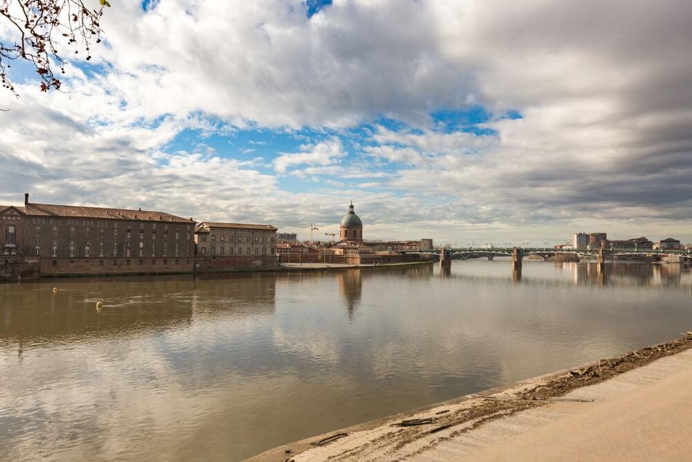Uitzicht bij Quai de la Daurade in Toulouse met de rivier de Garonne op de voorgrond, de bekende brug en historische gebouwen op de achtergrond. Wit/grijze wolken in de lucht met hier en daar wat blauw.