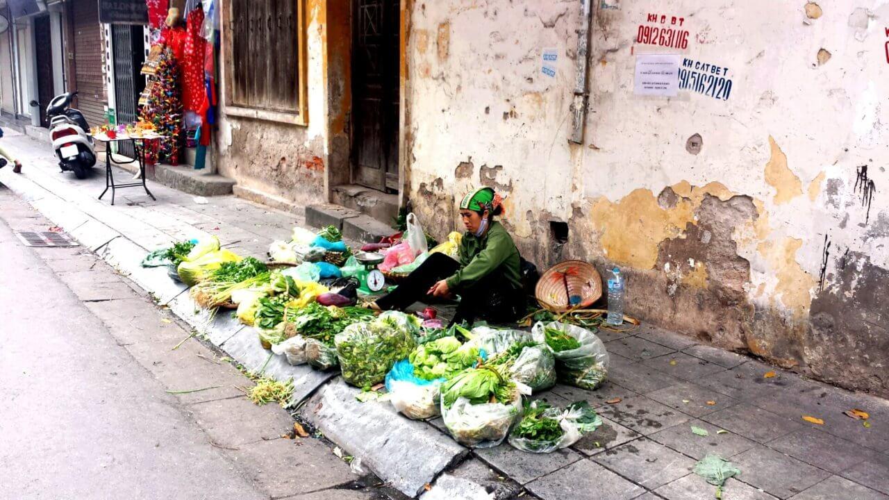 Vrouw verkoopt allerlei soorten groene groenten aan de straatkant in Hanoi en zit achter de groenten op de grond.