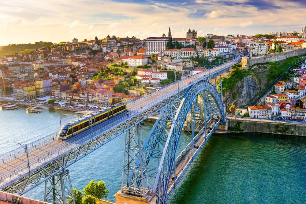 De bekende brug in Porto waar een trein overheen rijdt, de Douro rivier eronder en de stad zelf op de achtergrond.