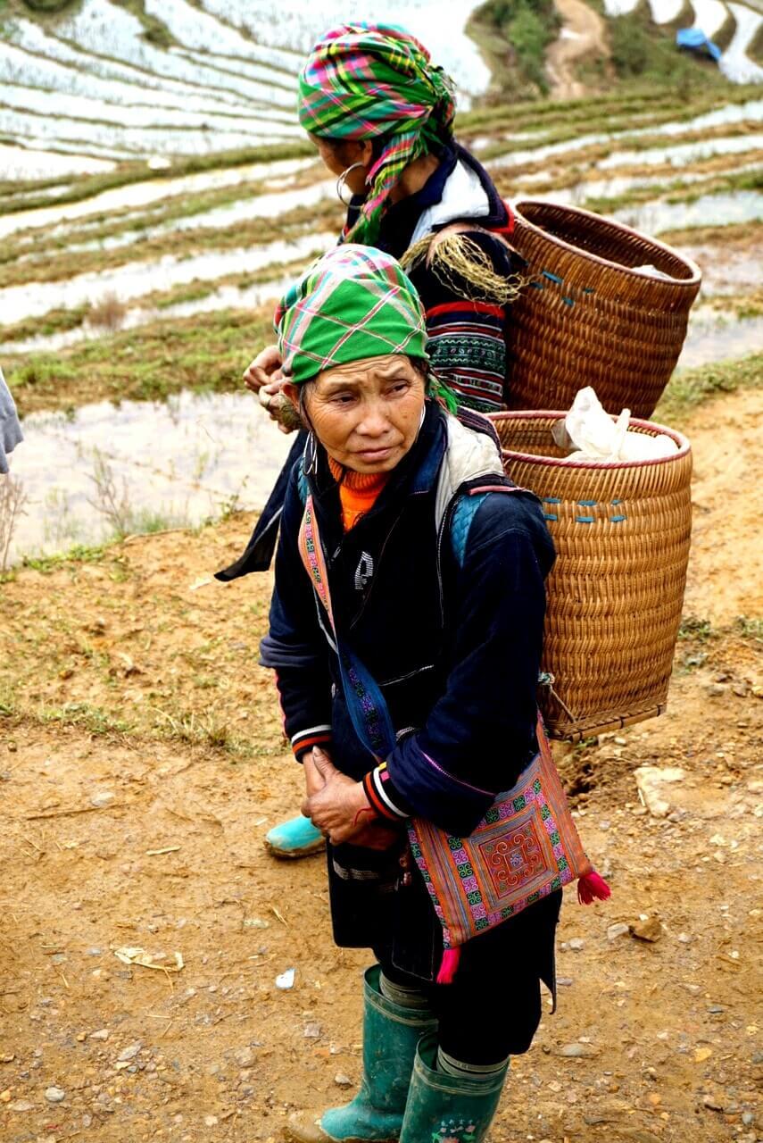 Vietnamese vrouw van een bergstam in Sapa, staat met haar traditionele kleding aan en een rieten mand op haar rus voor zich uit te staren. achter haar staat nog een vrouw in dezelfde klederdracht.