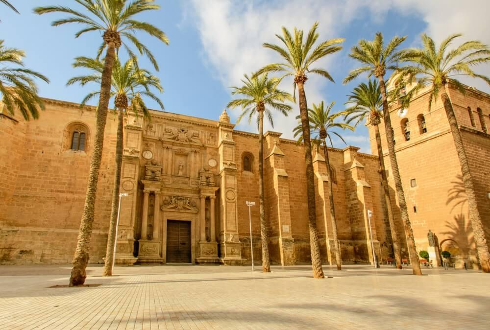 Prachtige kathedraal van Almeria, met een stuk of 9 palmbomen ervoor, een verlaten pleintje en blauwe lucht met enkele wolkjes op de achtergrond.