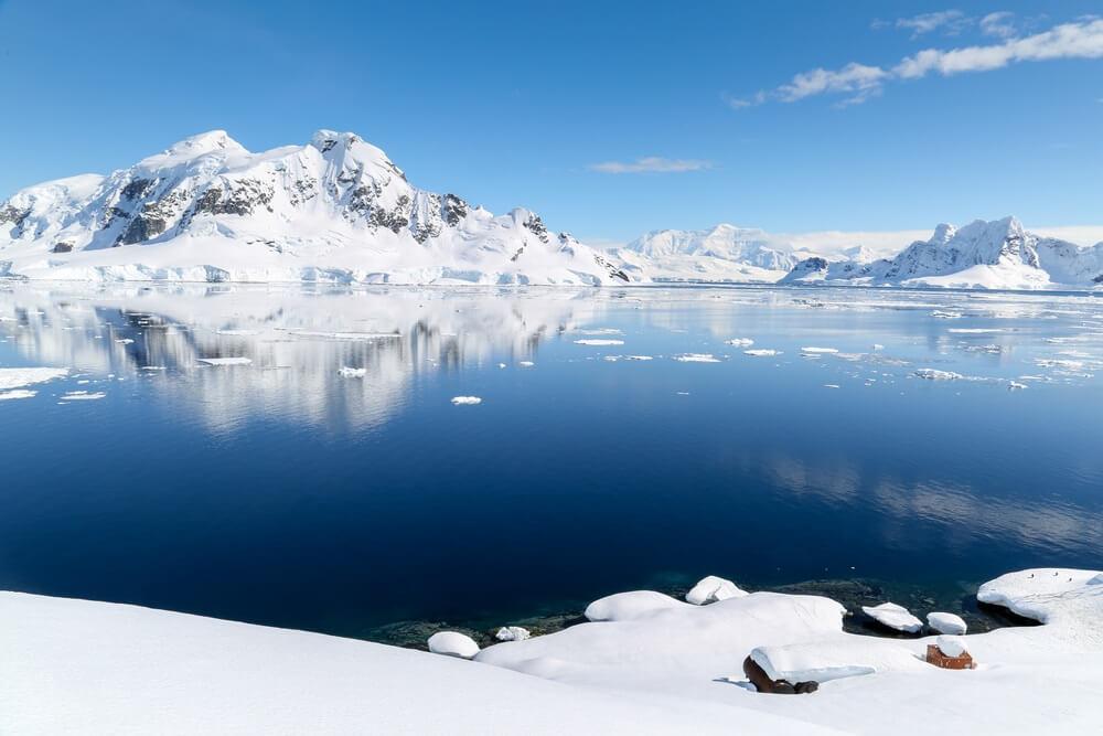 Zonnige dag in Antartica, blauw meer met besneeuwde bergen op de achtergrond, strakblauwe lucht.
