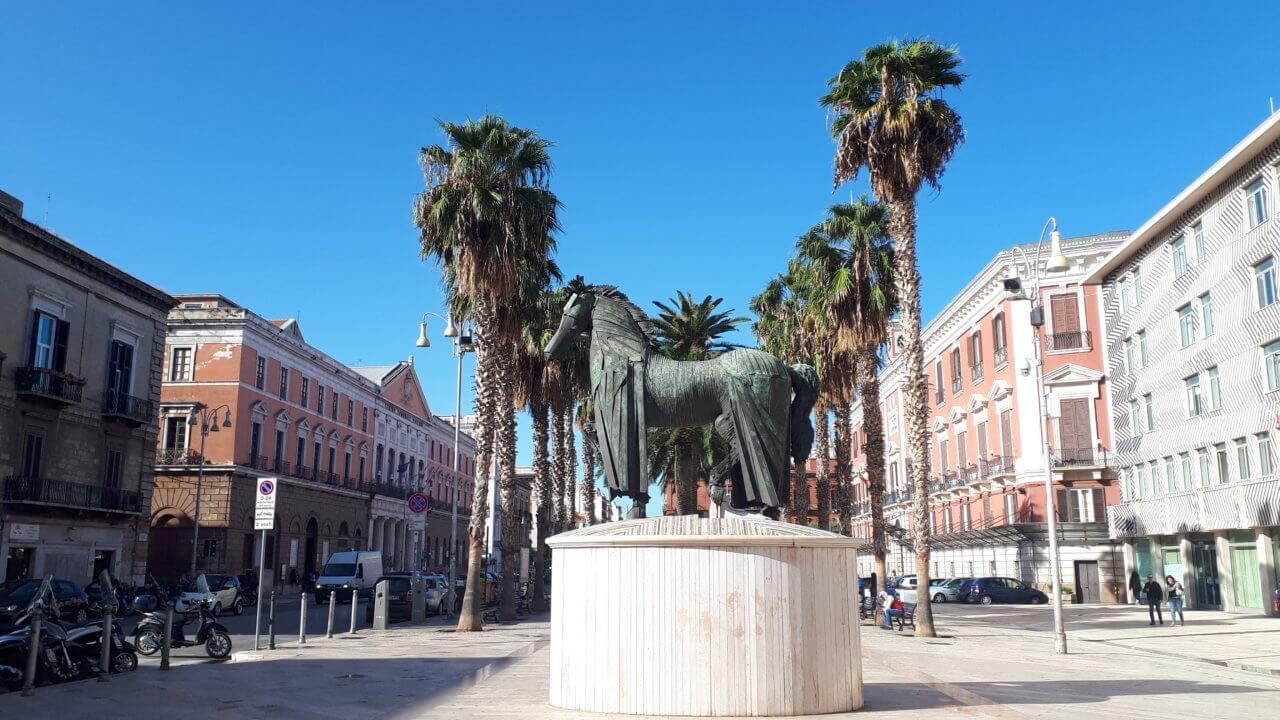 Het nieuwe centrum van Bari. één lage brede straat met daarlangs gebouwen en palmbomen. Op de voorgrond staat een beeld van een paard. Strakblauwe lucht op de achtergrond.
