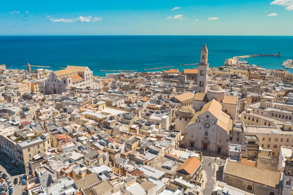 Overzicht van Bari, Italië. Witte gebouwen met rode daken en een azuurblauwe zee op de achtergrond.