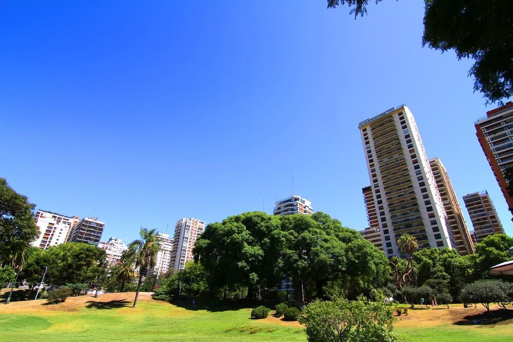 Park en Plaza de Barrancas i Buenos Aires, Belgrano. Groen grasveld met groene bomen en skyscrapers op de achtergrond.
