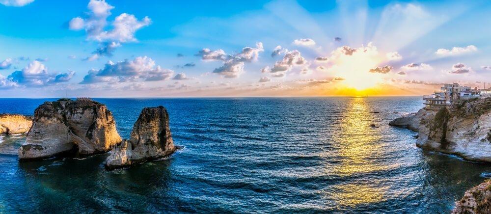 Prachtige zonsondergang aan de kust van Beirut met de Raouche Rock in het water.