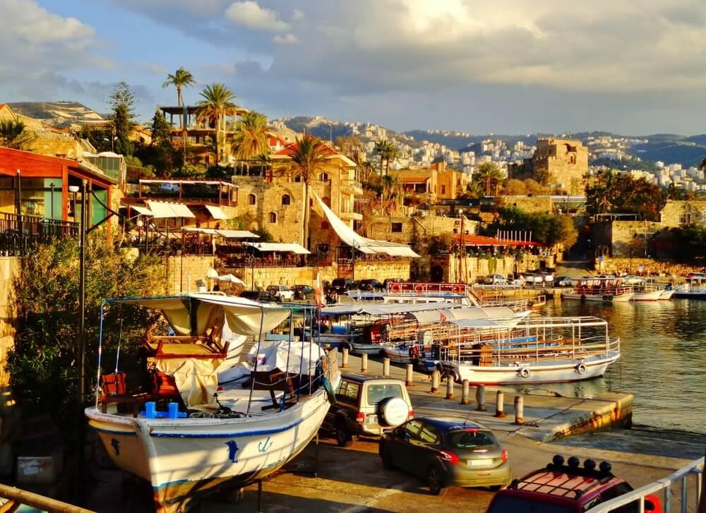 Oude stad van Byblos, de haven met bootjes aan de waterkant. Daarachter oude gebouwen en huizen en aan de horizon heuvels met witte dorpjes.